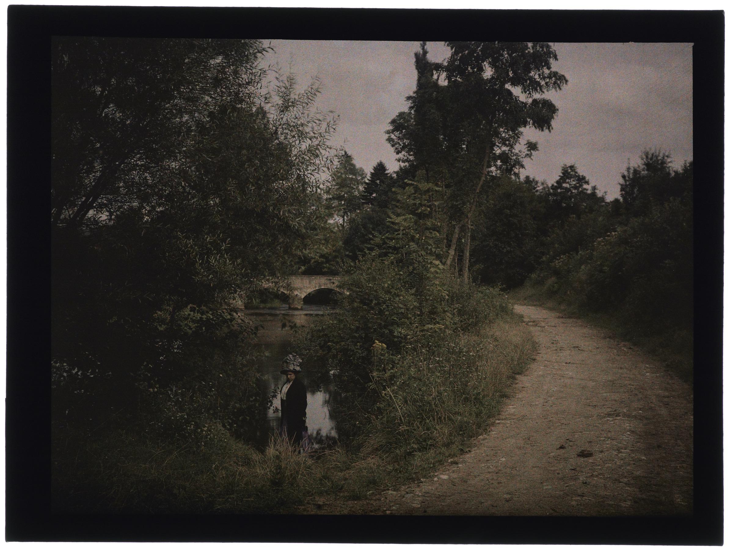 Une ou deux femmes avec le village en arrière plan ou un pont