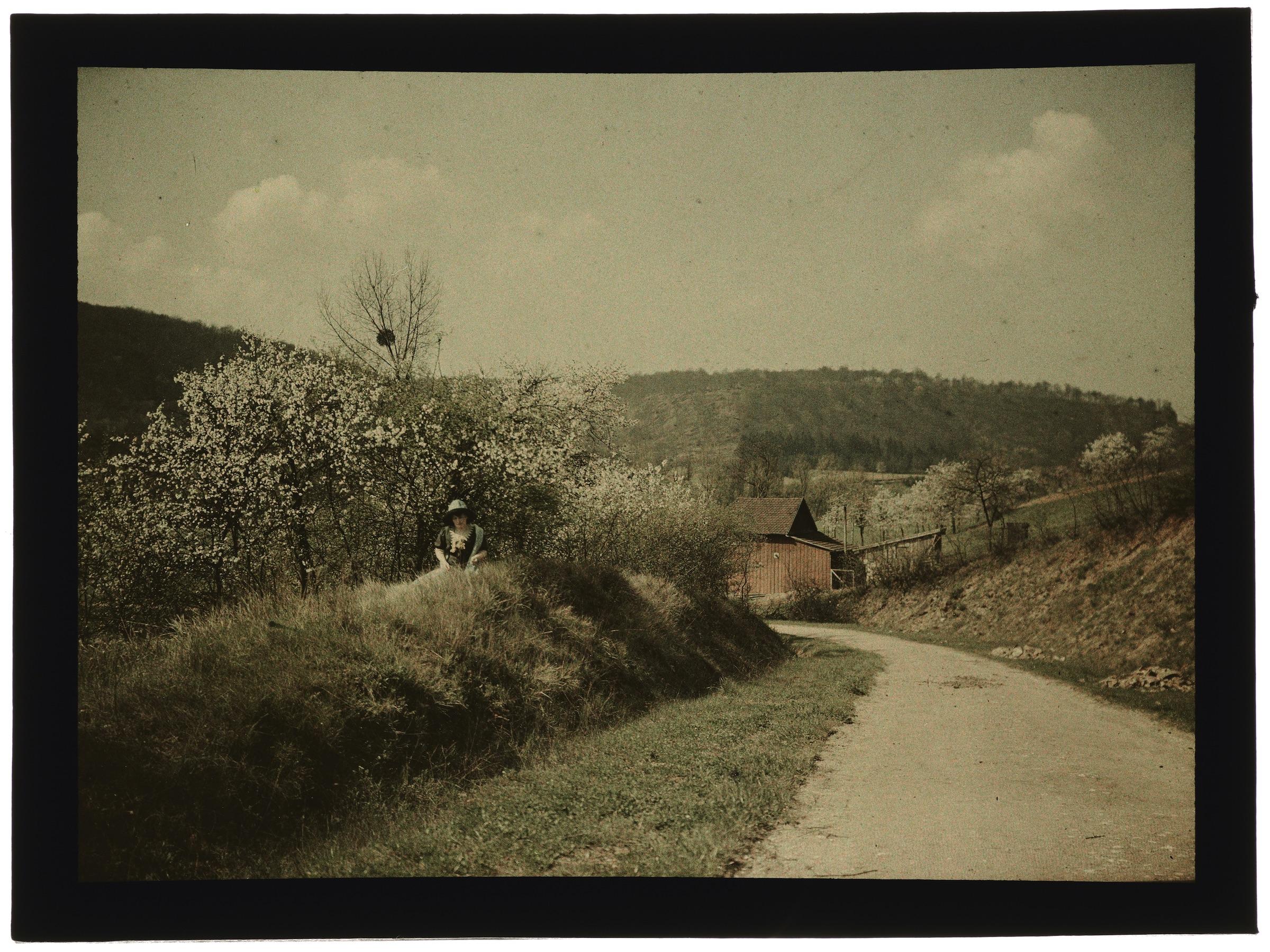 Femme dans la campagne avec village en arrière plan