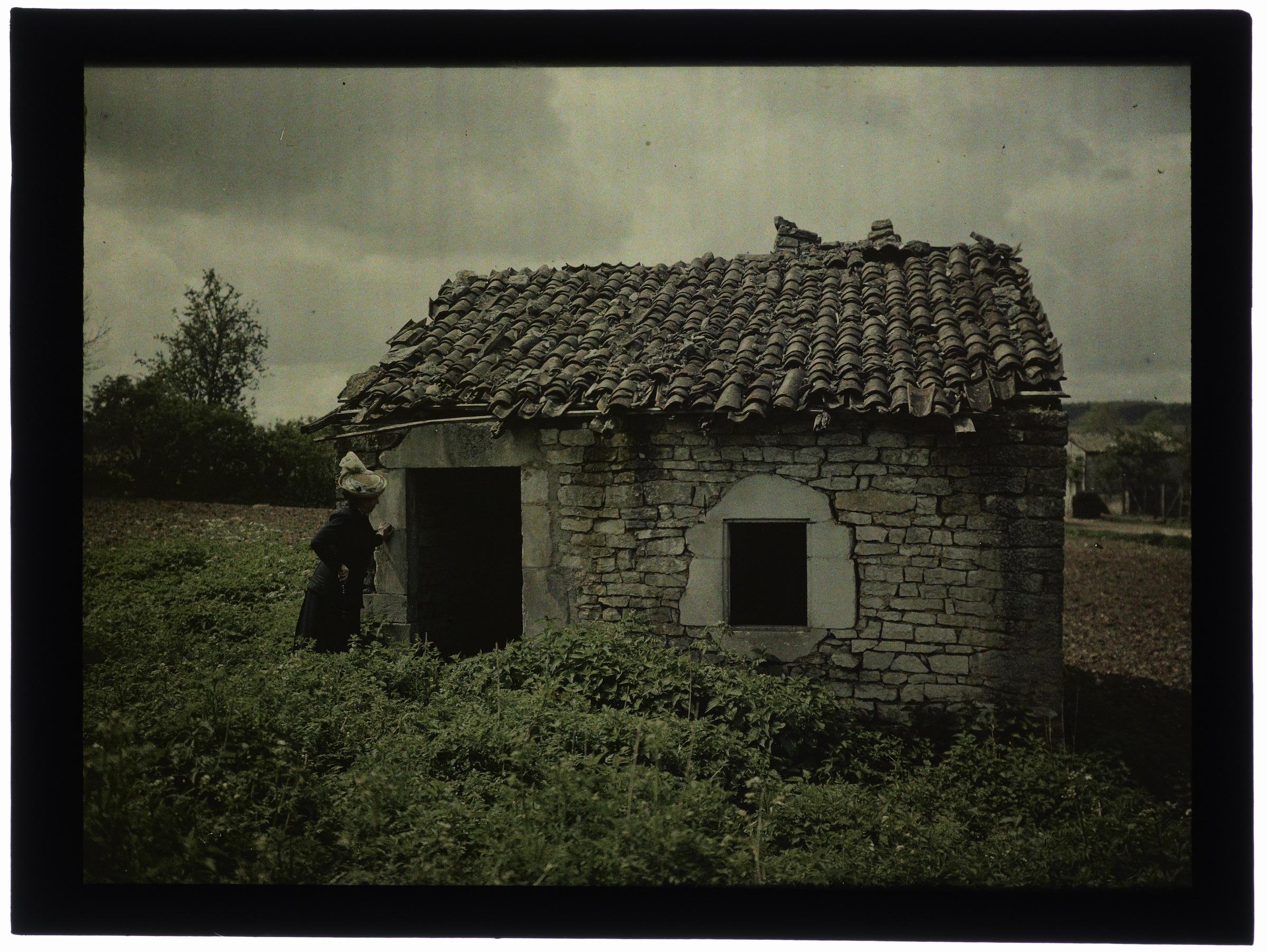 Femme à côté d'une maison en ruine