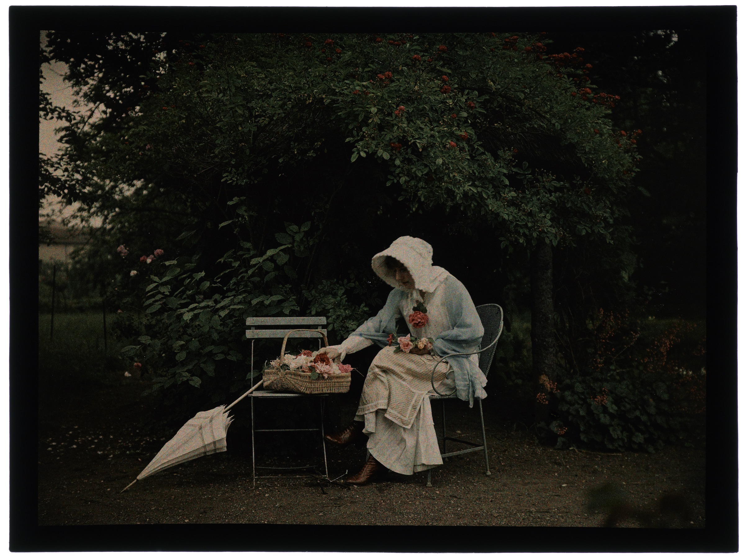 Femme en hâlette au jardin fleuri