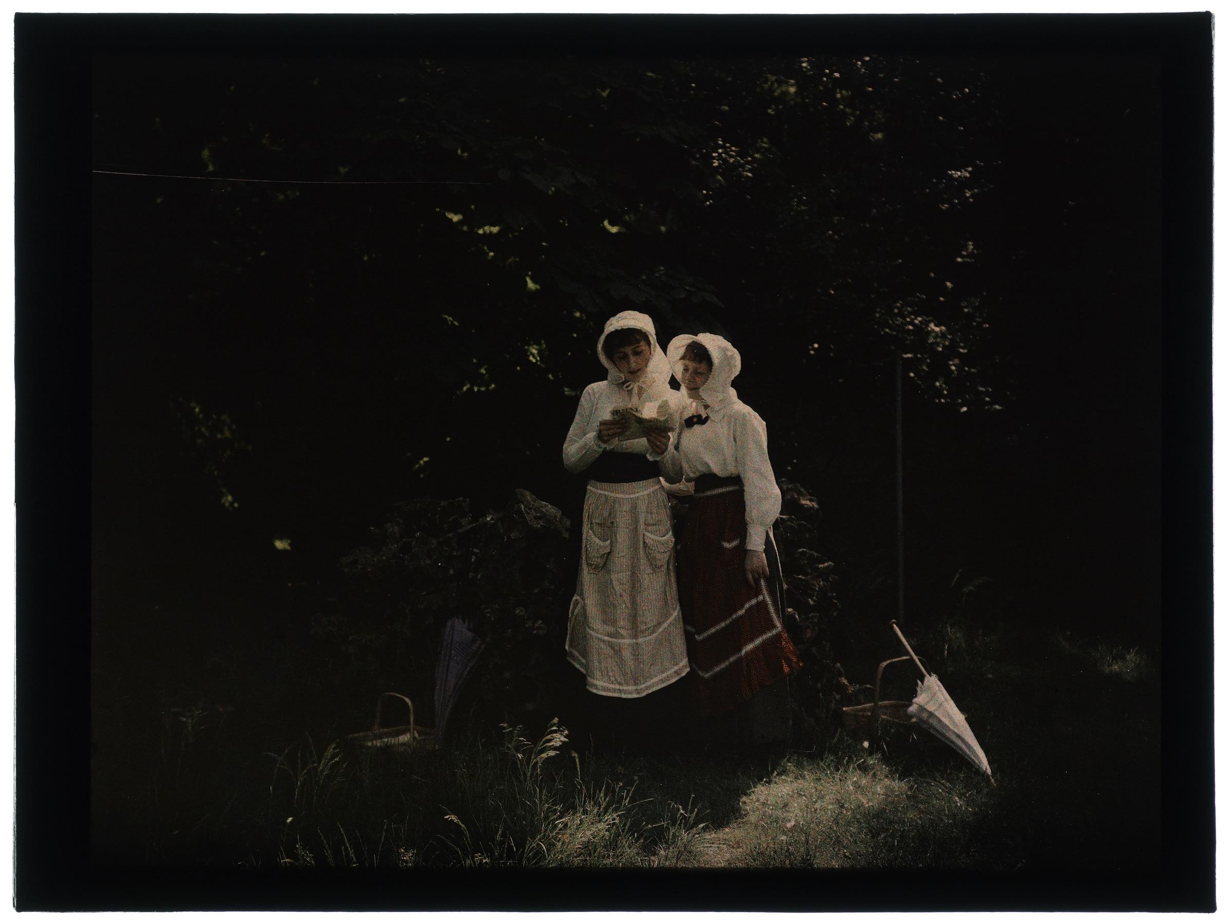 Deux femmes en hâlette au jardin fleuri