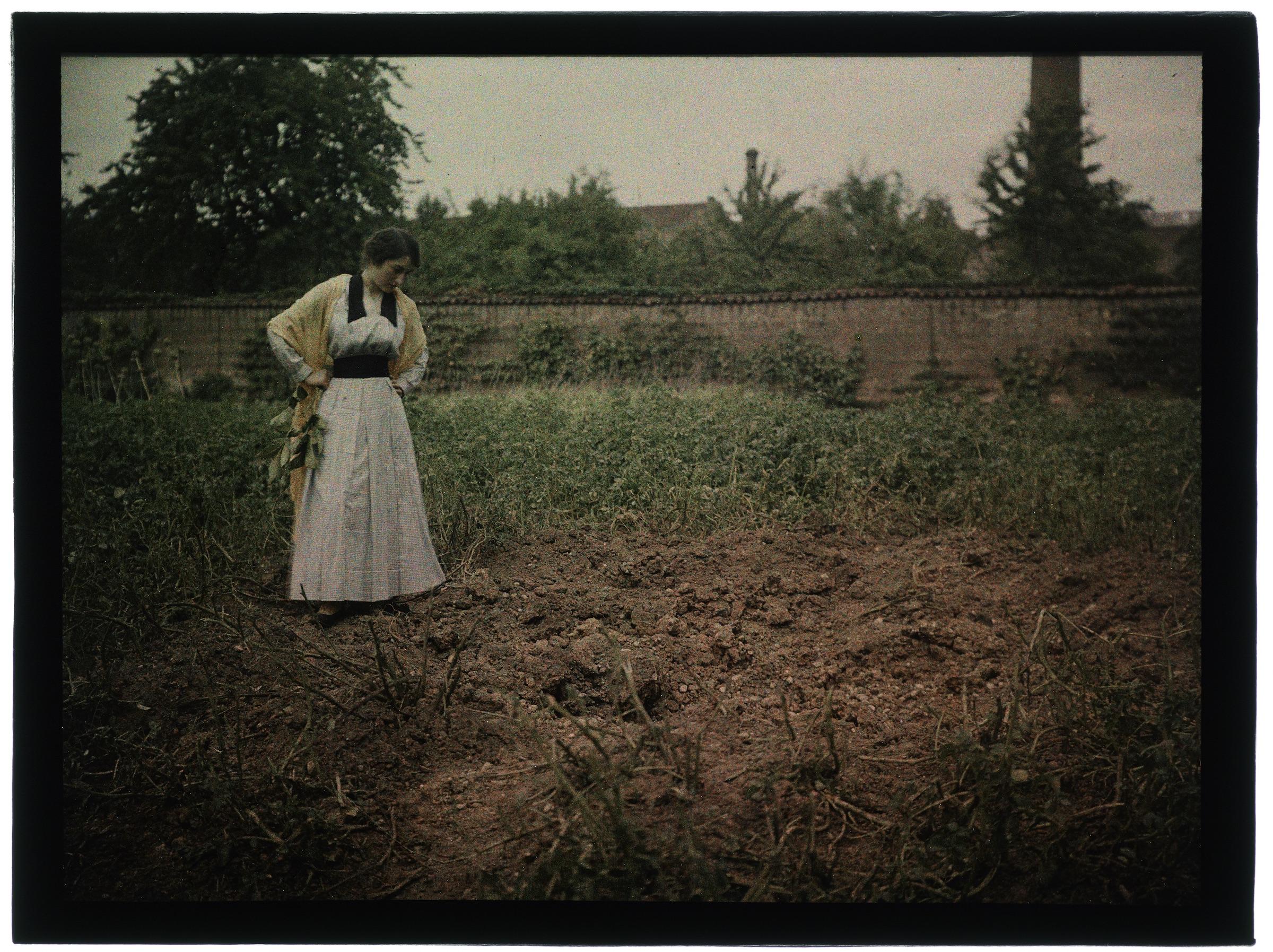 Femme au jardin devant un trou