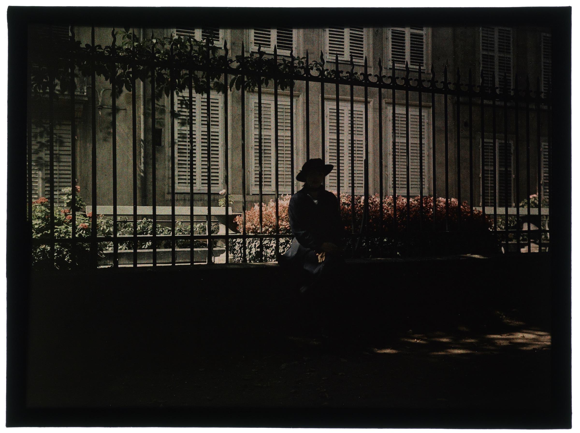 Femme assise sur le muret d'une grille de maison de maître